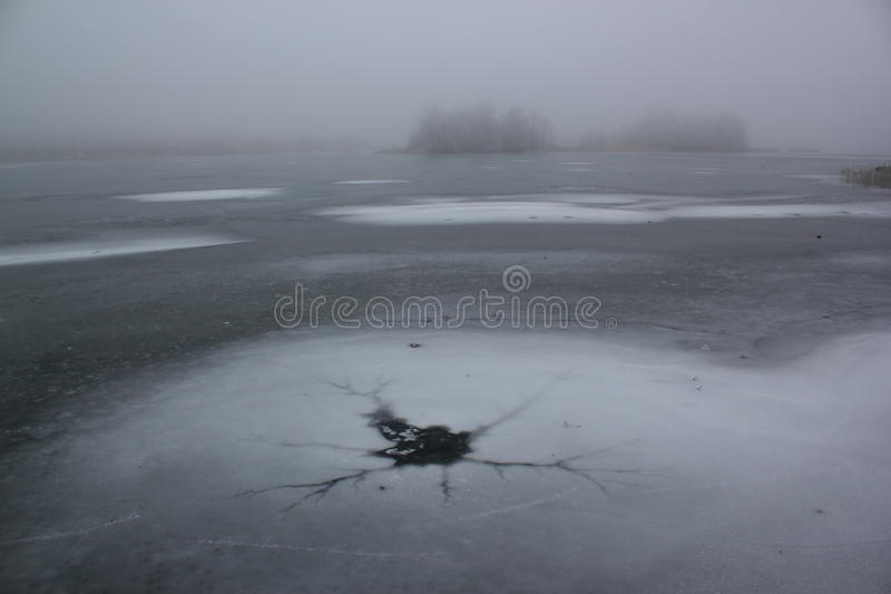 Hielo-agujero en Misty Frozen Lake Winter imagen de archivo