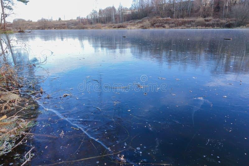 Hielo azul en la superficie de un lago del bosque La nieve todavía no ha caído Invierno temprano fotografía de archivo