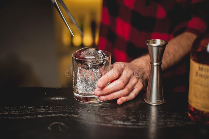 Hielo de colada del camarero en vidrio Camarero que prepara la bebida del cóctel fotos de archivo libres de regalías
