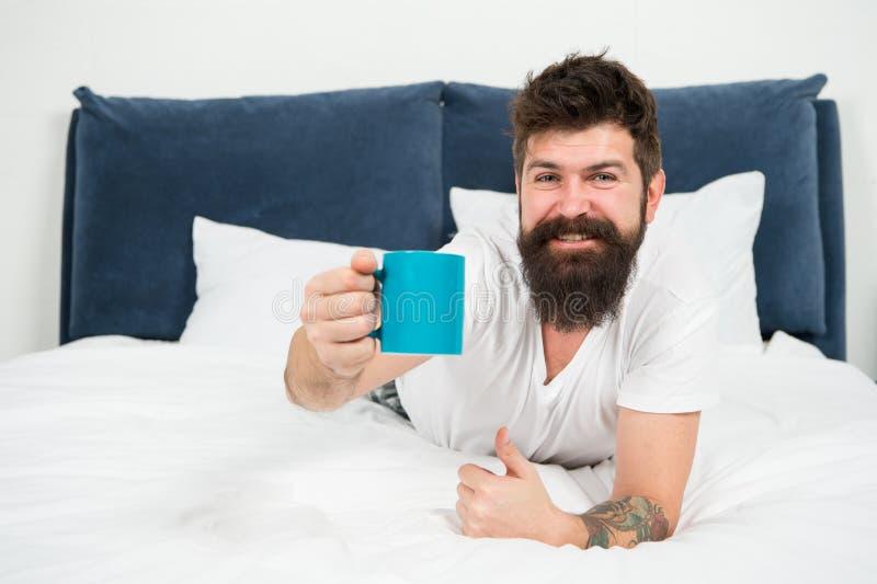 Hier is uw ochtendkoffie brutale slaperige mens in slaapkamer rijp mannetje met baard in pyjama op bed in slaap en wakker royalty-vrije stock foto