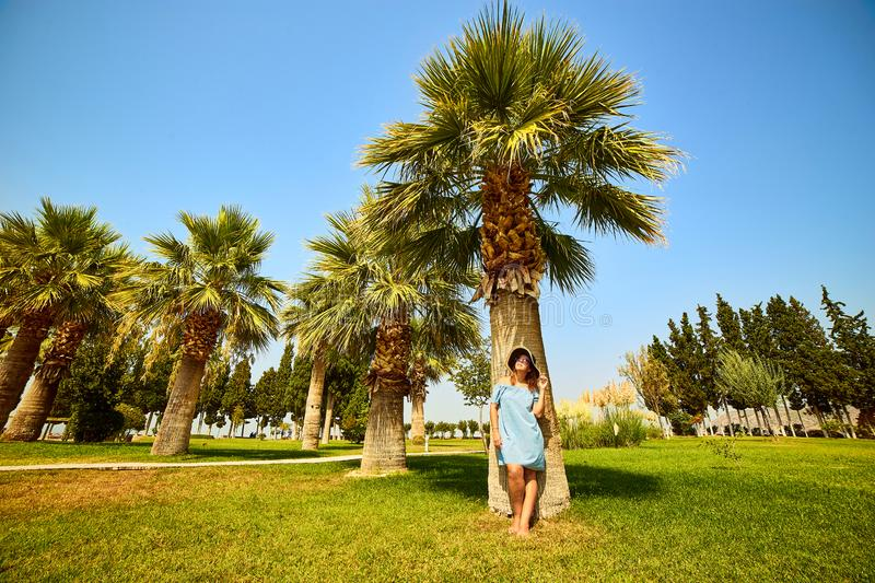 Hierapolis, Pamukkale, Turkey: Woman in hat standing under a palm tree and enjoy sunny day stock image