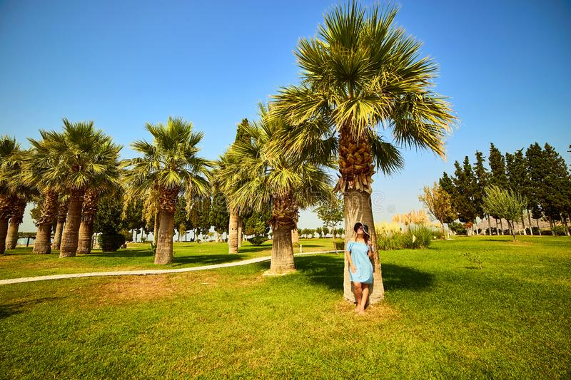 Hierapolis, Pamukkale, Turkey: Woman in hat standing under a palm tree and enjoy sunny day stock photo