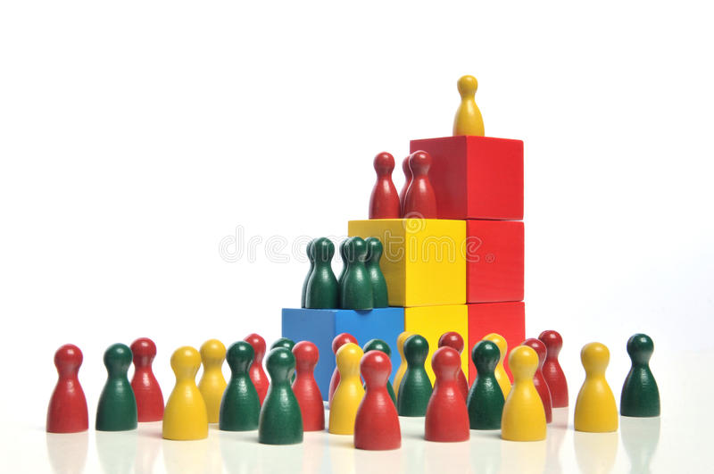 Hierarchy. Multicolored wooden toy blocks and figures on white background stock photo