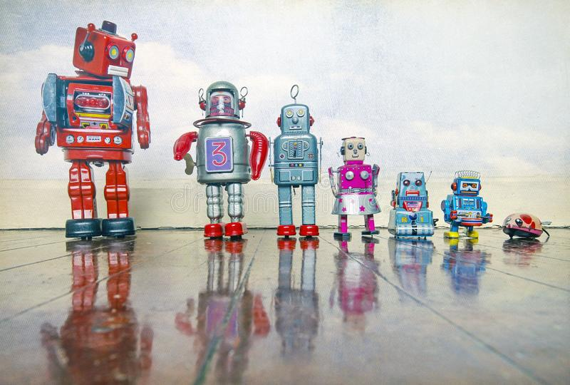 Hierarchy of tin toys from big red robot to little mouse. On a wooden floor with reflection royalty free stock photos