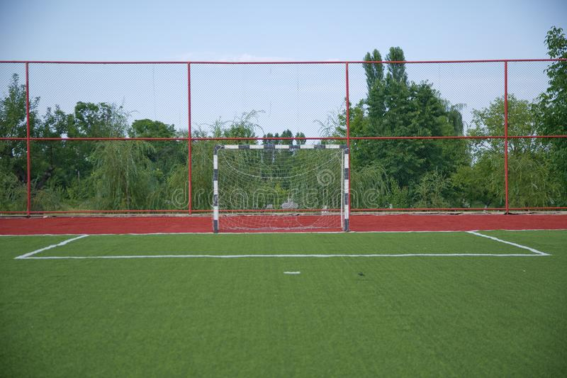 Hierba artificial de Mini Football Goal On An Meta del fútbol en un césped verde Campo de fútbol cerca de la cerca en el día sole foto de archivo