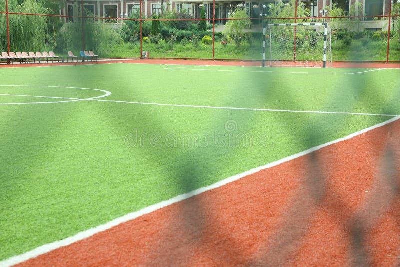 Hierba artificial de Mini Football Goal On An Meta del fútbol en un césped verde Campo de fútbol cerca de la cerca en el día sole fotos de archivo
