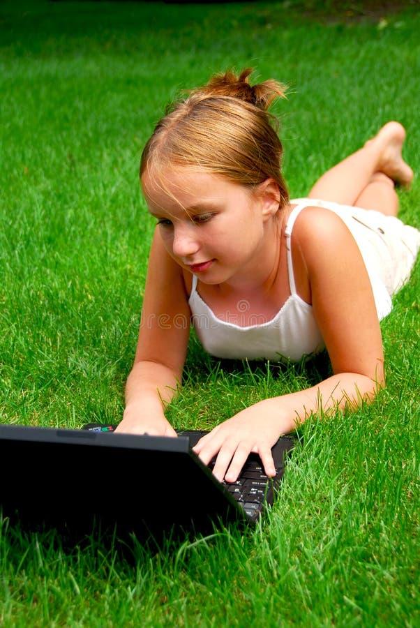 Hierba del ordenador de la muchacha imagenes de archivo