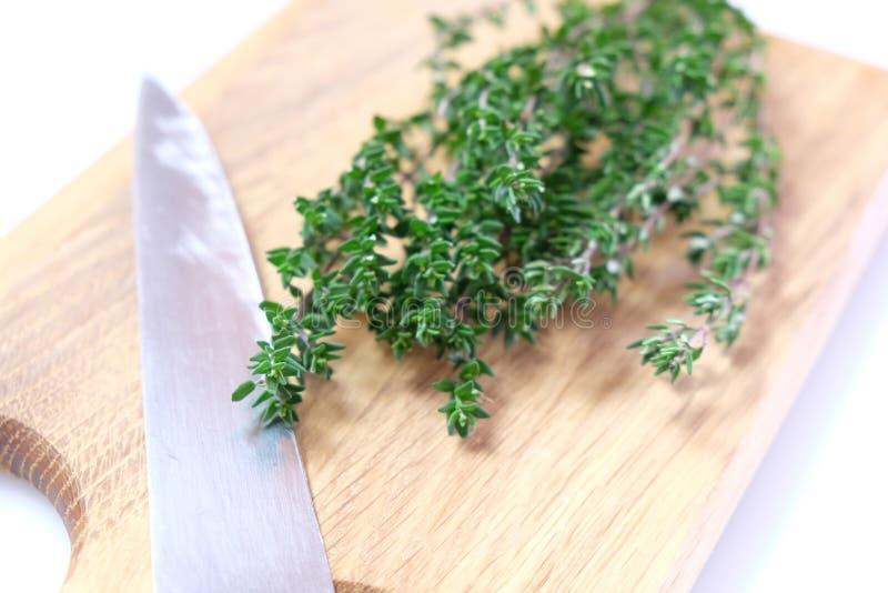 Hierba orgánica del tomillo en la tajadera con el cuchillo fotos de archivo