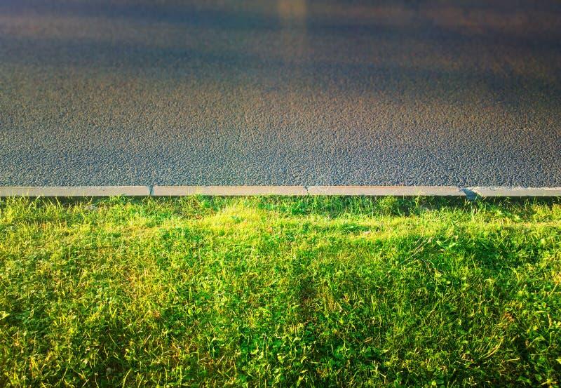 Hierba verde en fondo de la ciudad de la acera del camino imágenes de archivo libres de regalías