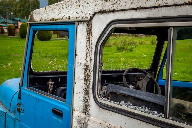 Hierba verde enorme azul abandonada del coche del vintage ningunos cristales de ventana rotos fotografía de archivo libre de regalías