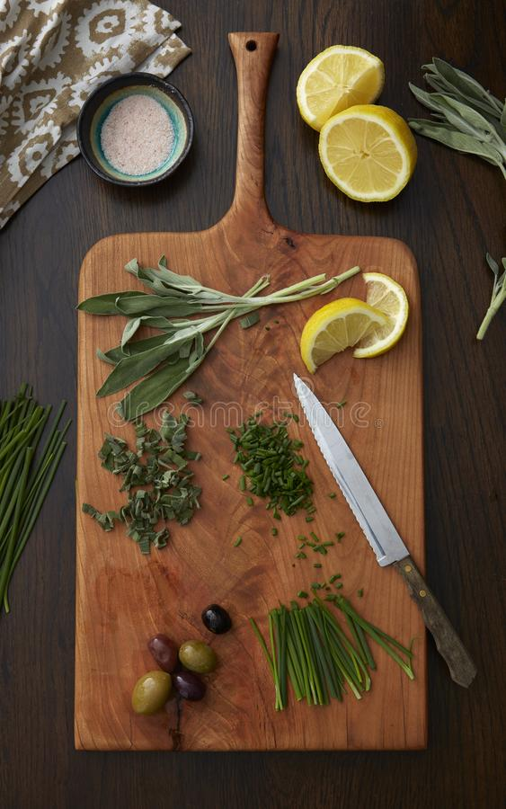Hierbas, aceitunas y limones siendo cortado y preparados en una tabla de cortar de madera foto de archivo libre de regalías