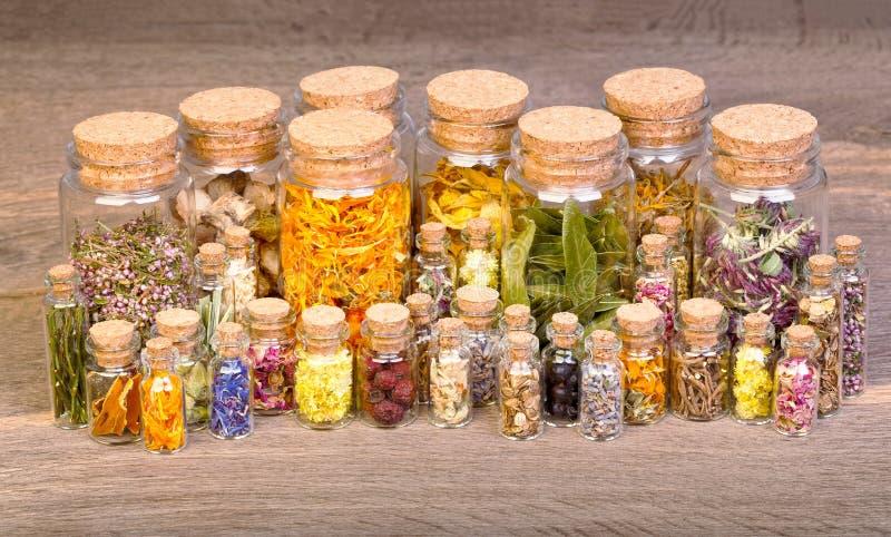 Hierbas curativas en las botellas para la medicina herbaria en la tabla de madera vieja fotos de archivo