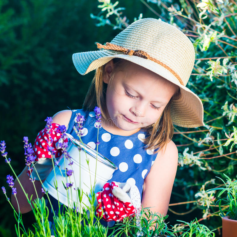 Hierbas de riego de la muchacha linda Niño que toma el cuidado de plantas Niño con foto de archivo libre de regalías