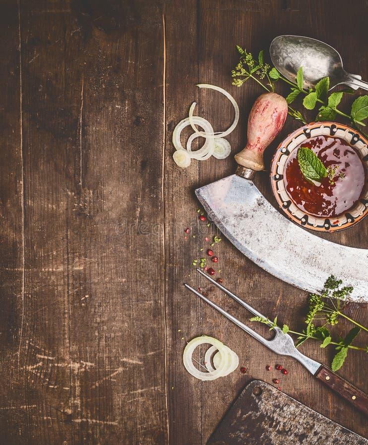 Hierbas, especias y salsa con las herramientas envejecidas de la cocina en el fondo de madera rústico, visión superior, frontera  fotos de archivo