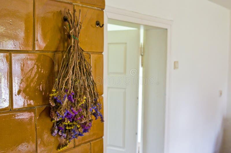 Hierbas violetas que cuelgan en el horno viejo de la casa fotos de archivo