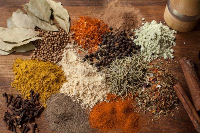Hierbas y composición de las especias que cocina los ingredientes en un tablero de la mesa de madera fotografía de archivo