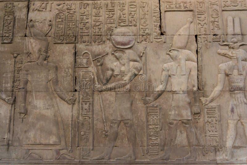 Hieroglyfiska carvings på de yttre väggarna av den egyptiska templet fotografering för bildbyråer