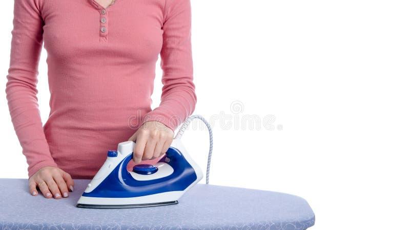 Hierro azul disponible de la mujer en el tablero que plancha foto de archivo libre de regalías