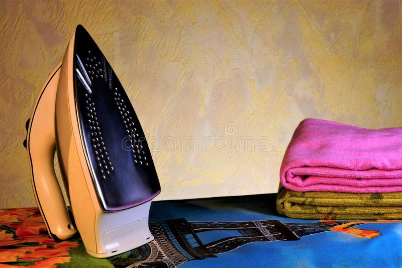 Hierro eléctrico, tablero que plancha y lino Planchando con el avión calentado del lenguado del hierro, la tela adquiere un liso fotos de archivo libres de regalías