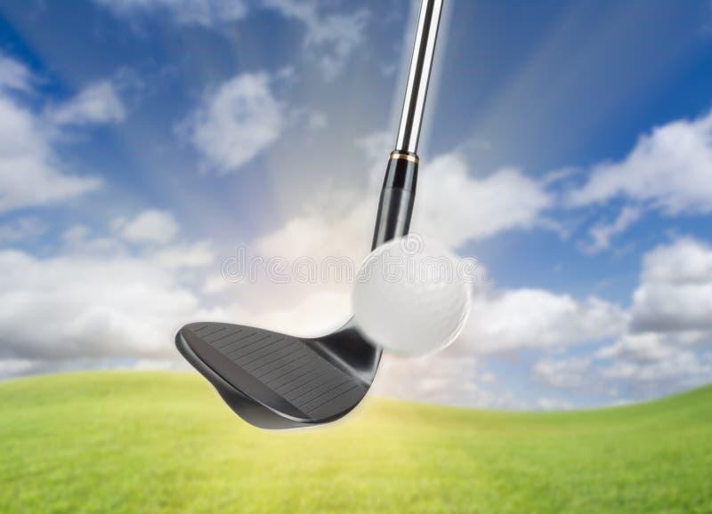 Hierro negro de la cuña de Golf Club que golpea la pelota de golf contra fondo de la hierba y del cielo azul imagen de archivo
