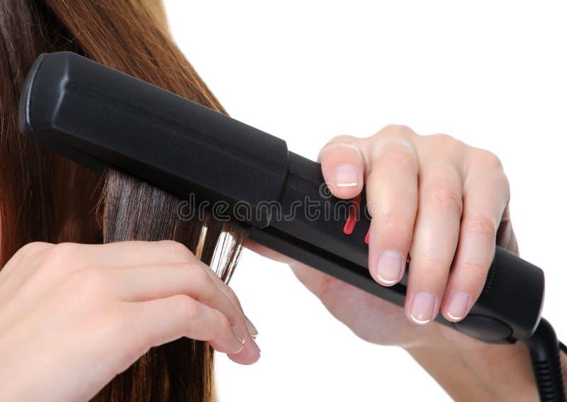 Hierro plano que se aplica en el pelo trigueno femenino fotografía de archivo libre de regalías