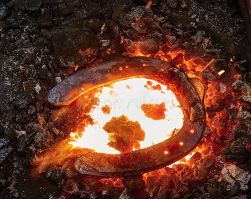 Hierro que se calienta en el fuego para crear la herradura en abvil imagenes de archivo