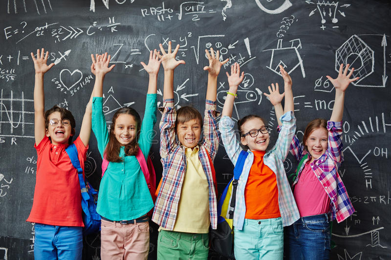 High achievers. Ecstatic learners raising hands against blackboard stock images