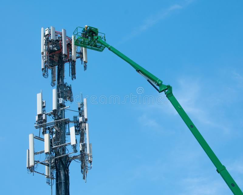High in the air, workmen maintain a cell tower stock image