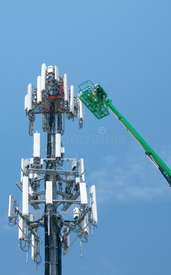 High in the air, workmen maintain a cell tower royalty free stock images