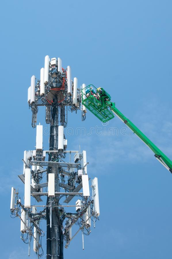 High in the air, workmen maintain a cell tower royalty free stock photography