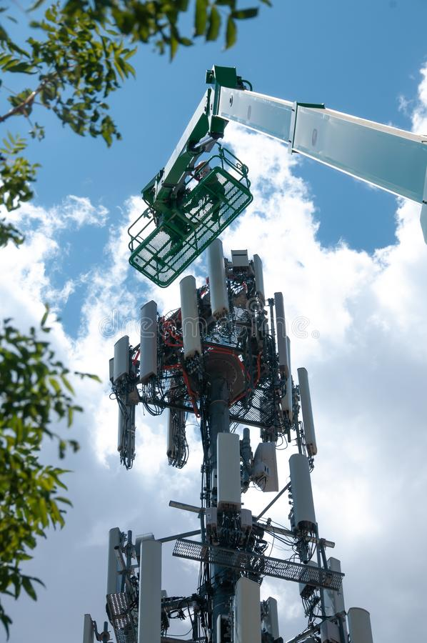 High in the air, workmen maintain a cell tower royalty free stock image
