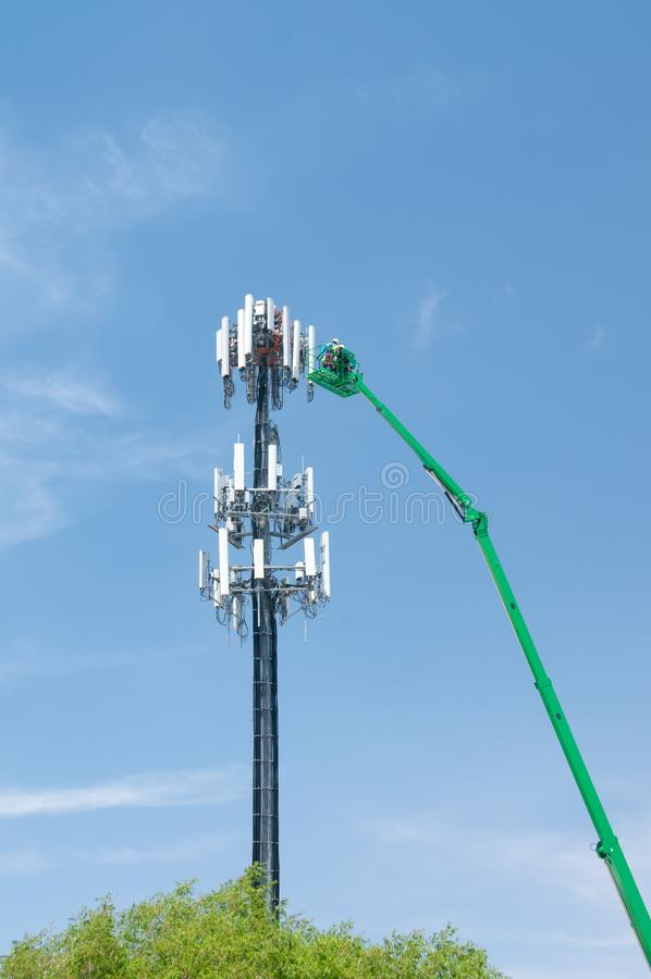 High in the air, workmen maintain a cell tower stock photography
