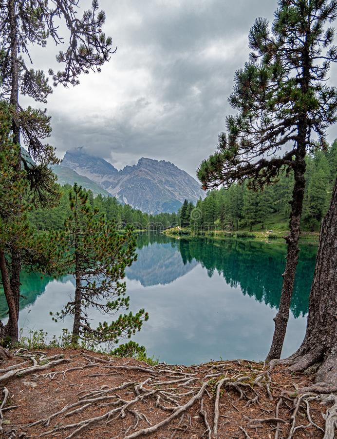 A high alpine mountain lake perfectly reflects the surrounding mountains royalty free stock photos
