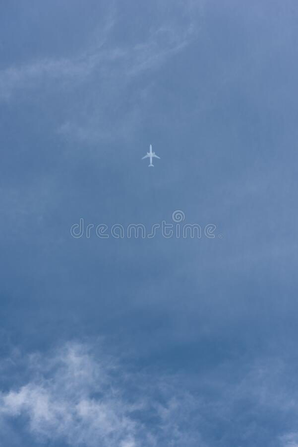 High altitude jet aircraft traveling across blue sky stock photo