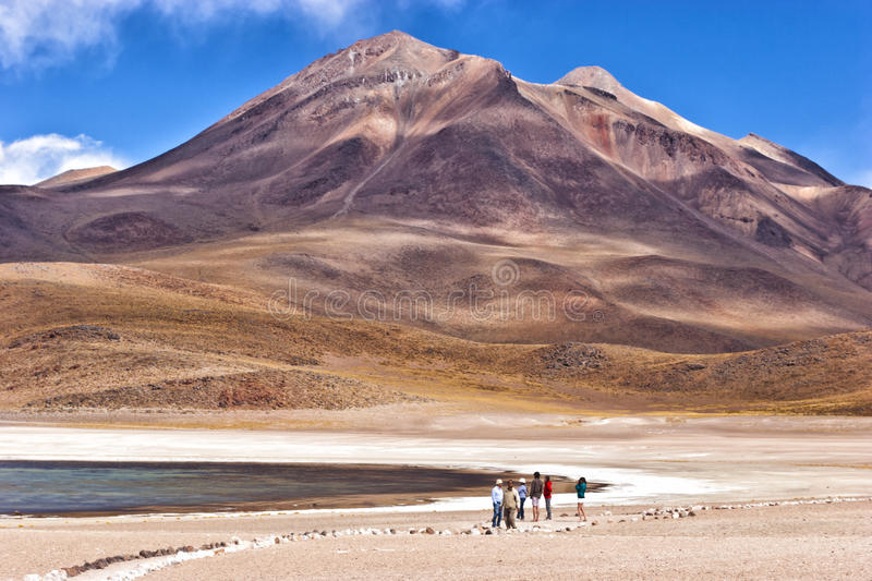 High altitude mountains with lakes in Atacama desert. Stone path to a lake near volcanic mountains in Atacama desert Chile royalty free stock photo