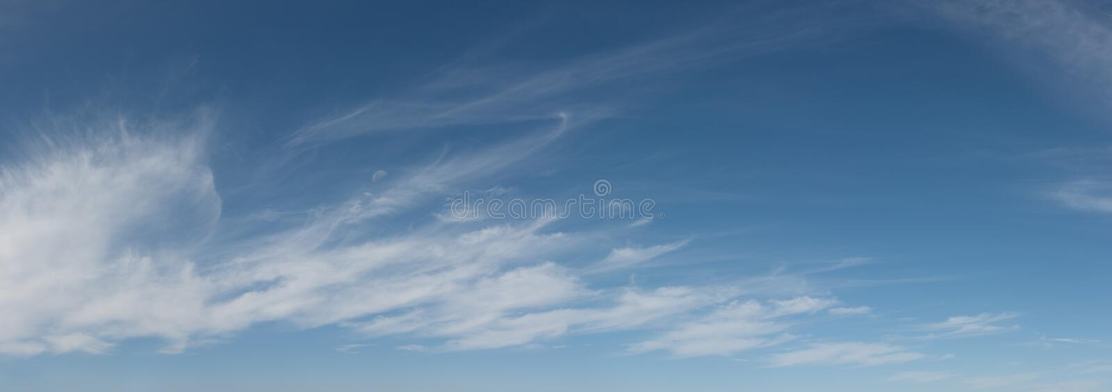 High altitude wispy clouds with half moon visible stock photo