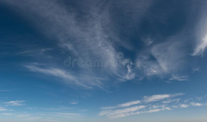 High altitude wispy clouds traveling across blue sky royalty free stock images
