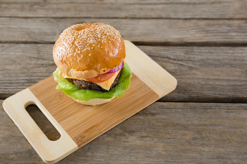 High angel view of hamburger with cheese on cutting board stock photography