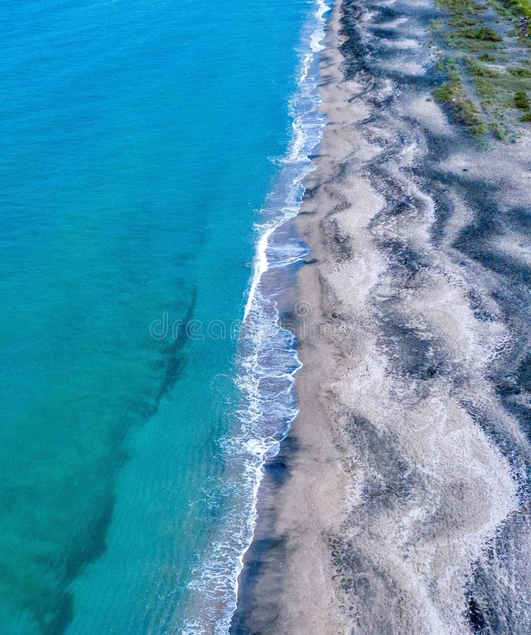 High angle aerial shot of a beautiful blue water beach waves hitting the shore stock photos