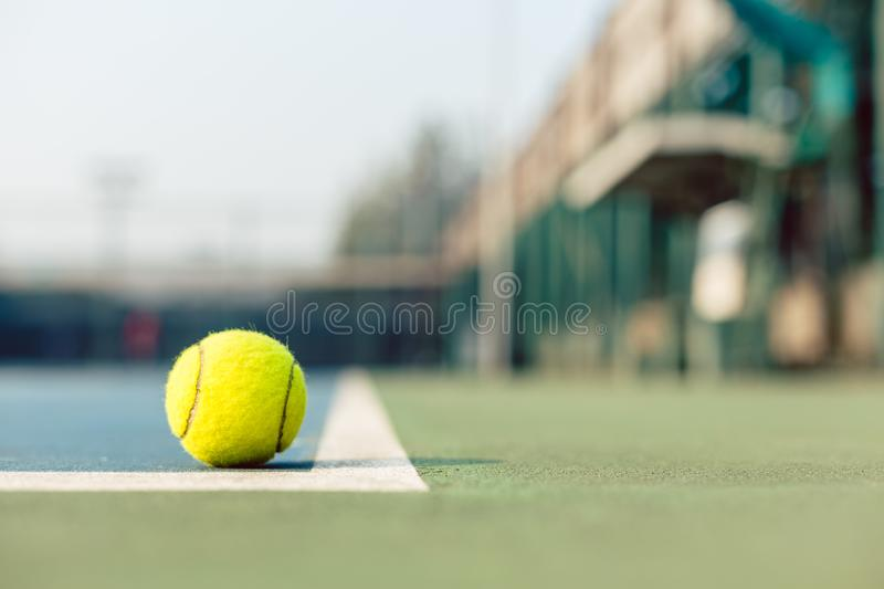 High-angle close-up of a fluorescent yellow tennis ball in the court. High-angle close-up of a fluorescent yellow tennis ball in the corner at the baseline on stock photos