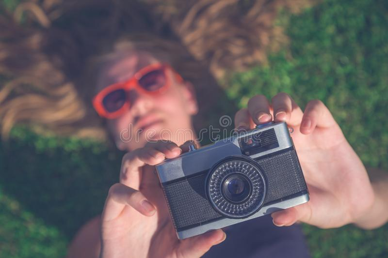 Female lying in grass and taking photo with retro camera stock photography