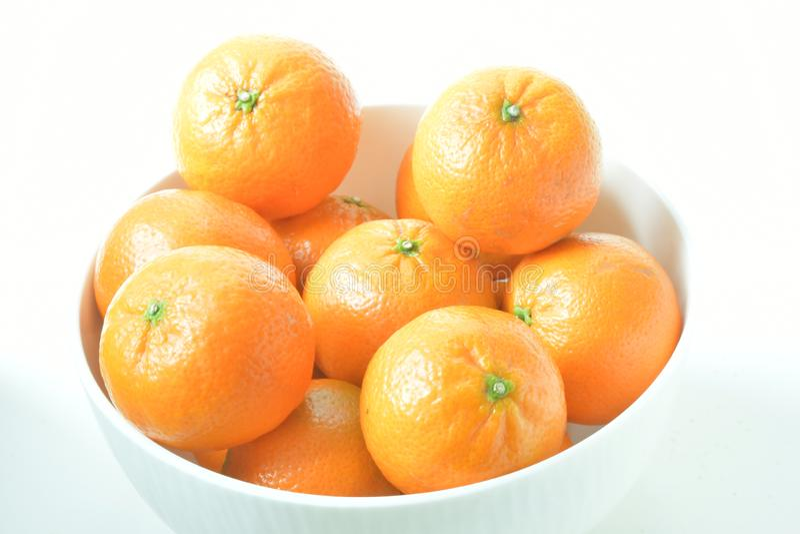 High angle close up of white bowl of mandarin oranges, against white background. Studio shot. High angle close up of white bowl of juicy mandarin oranges stock images
