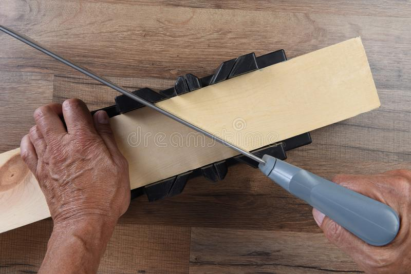 High angle closeup of a woodworker using a miter box and hand saw to cut a board at an angle.  royalty free stock image