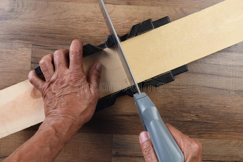 High angle closeup of a woodworker using a miter box and hand saw to cut a board.  royalty free stock photos