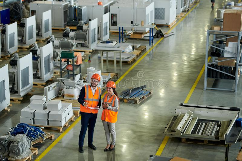 Factory Inspection. High angle full length portrait of cheerful young women wearing hardhat giving tour of production factory to inspector or investor, copy stock photography
