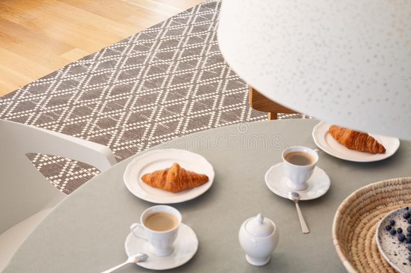 High angle on grey table with cups and croissants in scandi dining room interior. Real photo royalty free stock photography