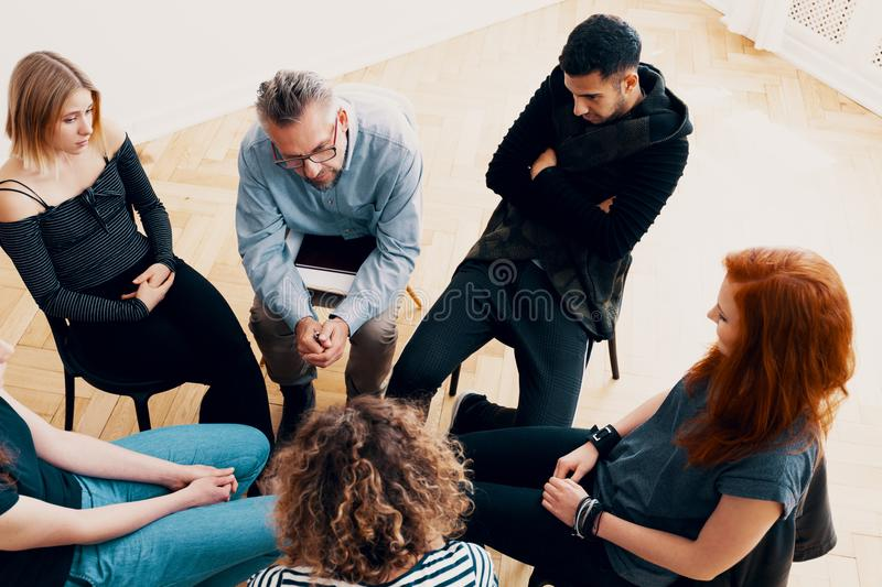 High angle of a group of teenagers sitting in a circle during ps. Ychotherapy stock photography