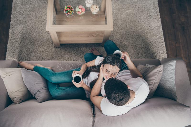 High angle photo of adorable pair in love holding hot beverage hands look eyes overjoyed sitting sofa indoors stock photography