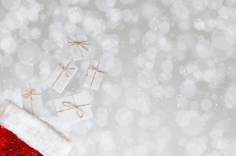 High angle photo of five Christmas presents wrapped in white paper and tied with white string and a stocking with a bokeh stock photography