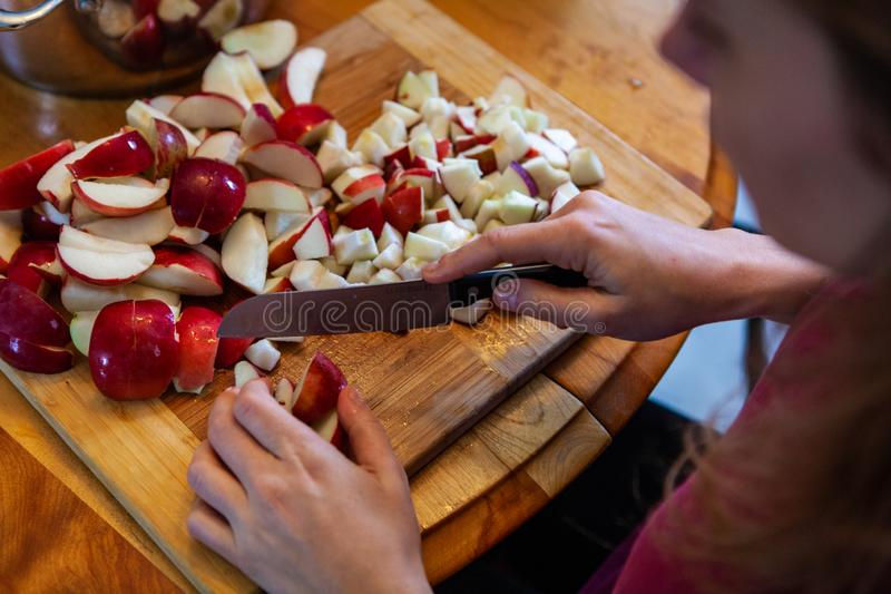Young woman cutting apples with a big knife, as seen from above stock images